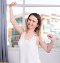 Smiling woman is doing morning exercises for her waist