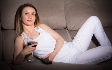 Young female is watching TV and sitting with white wine