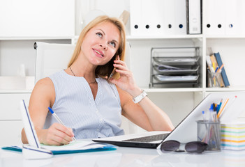 Portrait of  blond adult  girl in office talk on telephone
