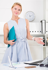 portrait of young  woman in dress with clipboard  in office