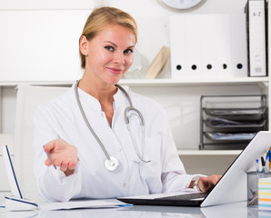 young  female doctor  working on computer in  home office