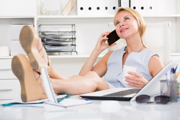 Portrait of  blond female in office talking on mobile