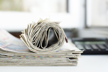 Folded and rolled newspapers and calculator. Paperwork on the desk at office. Journals with business news. Headlines and articles on tabloid pages, concept for market monitoring