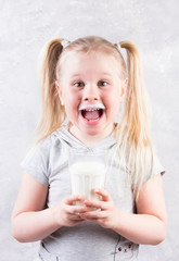 young cute little blonde girl in white t-shirt smiling and holding glass of milk