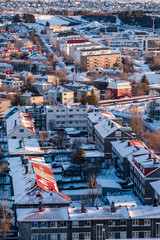 Aerial view of traditional urban development in Reykjavik, Iceland in winter with snow covered roofs viewed from above.