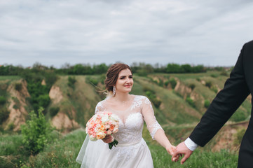 The young bridegroom leads the bride in front of the beautiful green hills. The bride and the groom are holding hands and looking at each other. Wedding in the hills.