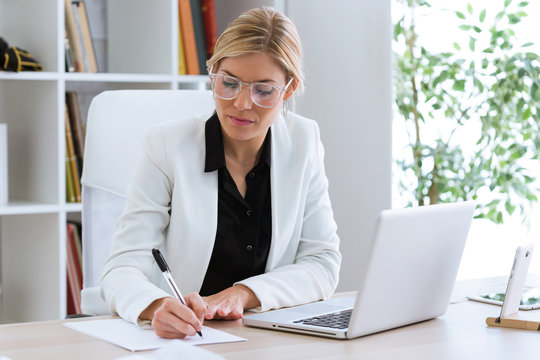 Beautiful young businesswoman writing and reviewing papers in the office.