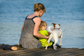 Mutter mit Kind und Hund am See
