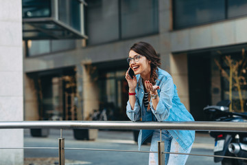 Young woman receiving good news over the phone in the city