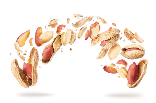 Dried peanuts crushed into pieces, frozen in the air on a white background