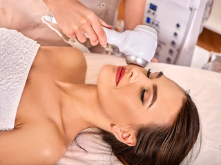 Ultrasonic facial treatment on ultrasound face machine. Woman receiving electric lift massage at spa salon. Electronic stimulation female muscles. Professional equipment microcurrent therapy. Recovery