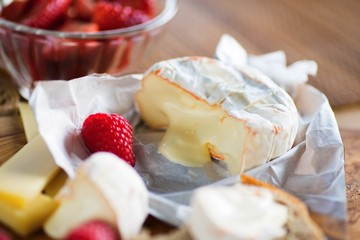 Cheese camembert and fruit on wooden kitchen board.