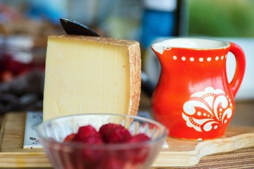 Piece of hard spicy cheese, red pitcher and raspberry.