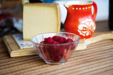 Hard cheese, raspberry and rustic red jug.