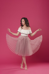 Young stylish girl in pink light skirt and white T-shirt on pink isolated background with place for text. The girl cheerfully dances and jumps like a ballerina
