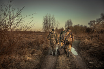 Group of men hunters with hunting equipment walking on country road   hunting season sunset