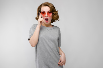 Charming young girl in a gray T-shirt on a gray background. Happy girl in red glasses