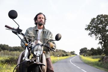 Adult bearded man sitting on motorbike and looking pensively away on background of road in green summer countryside.