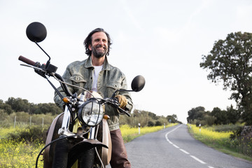 Happy smiling mature man in denim jacket and gloves sitting on motorbike enjoying travel and looking away on remote road.