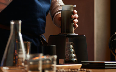 Bartender making alternative coffee using manual drip brewer, barista pouring water from kettle