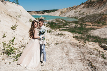 The bride in a beautiful dress hugging the groom in a light suit near the lake. Wedding couple standing on a sandy hill in the open air. A romantic love story. Azure-blue water on the horizon.