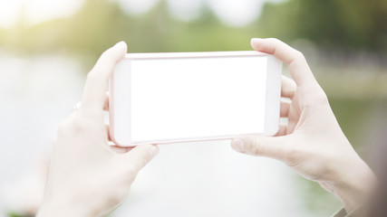 A girl female hands holding a smartphone taking a photo of the park