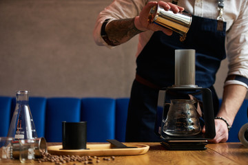 Barista prepare coffee at bar counter using different glassware and utensil, close-up