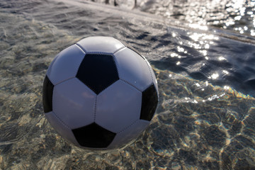 Classic soccer ball floats in water