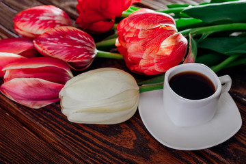 Cup of esspresso coffee and fresh tulips on wooden background. Good morning. Morning surprise