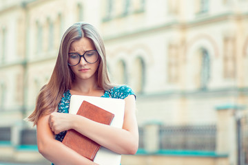 Student sad woman with glasses books, laptop in hand looking down in front of college