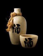 Sake bottle and cup isolated on black background