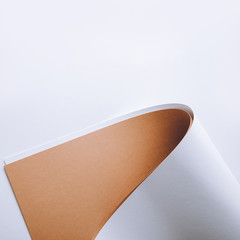 white and brown rolled paper sheets on grey background