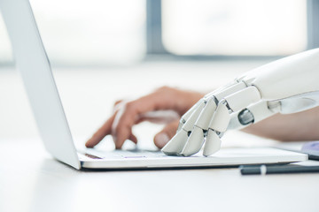 selective focus of human and robot hands typing on laptop at workplace Wall mural