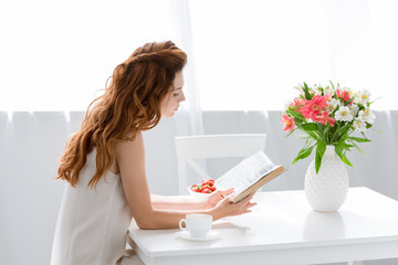 focused young woman reading book while sitting at table with coffee cup and flowers in vase
