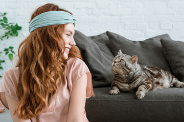 beautiful young woman smiling at adorable tabby cat at home