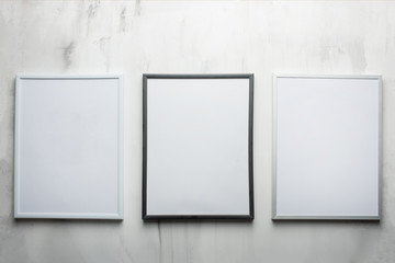 Three white frames on the wall background. The concept of design and font inscriptions and image placement