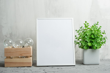 Empty white frame with a flower and bulbs on the wall background. The concept of design and font inscriptions and image placement