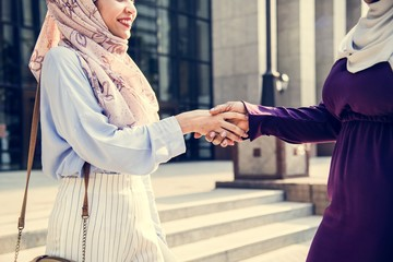 Islamic friends handshaking and smiling