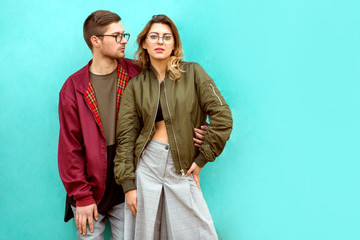 fashion couple in their glasses with burgundy clothes posing on a blue wall