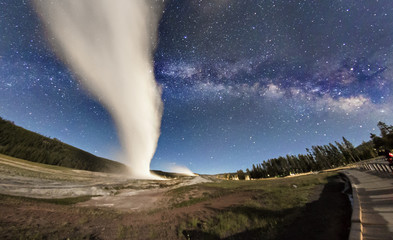 The Milky Way rising over Old Faithful erupting in Yellowstone National Park (Wyoming)