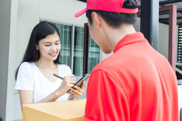 Young Asian Woman receive Pizza Box from  Delivery Man with Attractive Smiling at Home. People with Delivery Concept.