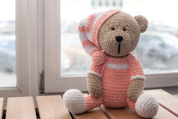 Knitted teddy bear isolated on wooden table