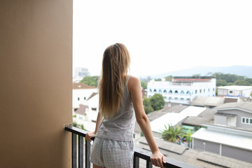 Young blonde girl wearing shorts and shirt standing on balcony and looking at buildings in background. Concept of fresh morning and mainly cloudy weather.