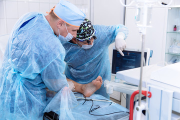 A team of doctors in the operating room conducts medical procedures. Surgeons in sterile clothing work in the hospital. Medical equipment in the clinic.