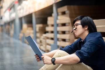 Young Asian man doing stocktaking thinking of product in cardboard box on shelves in warehouse by using paper and clipboard. physical inventory count concept