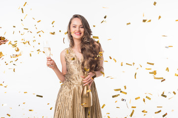 happy woman standing with champagne under falling golden confetti isolated on white