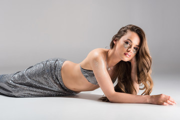 attractive woman lying on floor in silver skirt and top and looking at camera