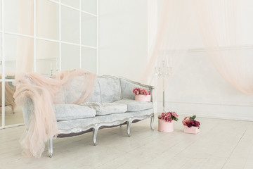 beautiful classical white interior with vintage sofa and mirror wall. Decorated with flower bouquets. Retro, classic