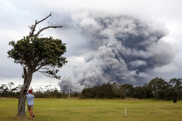 A man watches as ash erupts from the Halemaumau crater near the community of Volcano