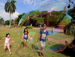 Children play with a large soap bubble created by a street performer at Rizal park in Luneta